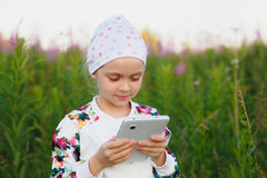 Little girl with digital tablet on the nature Royalty Free Stock Photography