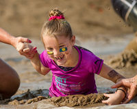 Little girl at the dirty dash going through the mud Royalty Free Stock Photography