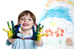Little girl with dirty hands painting a picture. Little girl with dirty hands painting her happy picture royalty free stock image