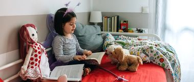 Girl disguised reading a book to her toys Royalty Free Stock Photography