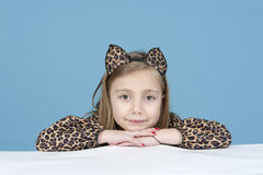 Little girl disguised as a leopard, isolated on blue Stock Photos