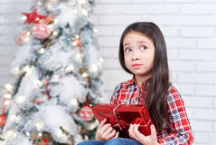 Little girl dissatisfied with Christmas gifts. Stock Photos
