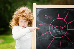 Little girl dissatisfied points on the board with a picture. Sad Royalty Free Stock Photos