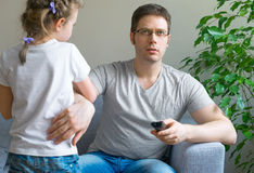 Little girl disturbing her dad. Little girl disturbing her dad while he is watching TV Royalty Free Stock Image