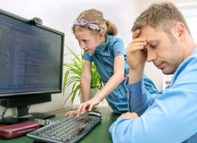 Little girl disturbing her dad. Little girl disturbing her dad while he is working at home Royalty Free Stock Photo