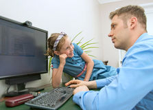 Little girl disturbing her dad. Little girl disturbing her dad while he is working at home Stock Images