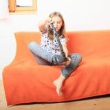 Little girl divesting socks. Little kid - girl divesting socks on sofa with orange cover royalty free stock photo