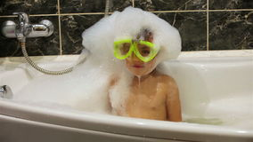 Little girl with a diving mask plays in a bathtub with foam stock video footage