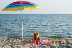 Little girl with diving mask under sunshade on beach Royalty Free Stock Photography