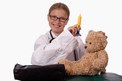 Little girl doctor. Cute little blond girl dressed up like a doctor holding a pretend needle and a brown teddy bear smiling royalty free stock photography