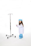 Little girl doctor with IV stand. Young child dressed in medical scrubs next to an IV stand and holding a stethoscope Royalty Free Stock Photos