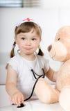 Little girl doctor with teddy bear Stock Photos