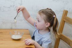 Little girl doesn`t want to eat porridge. Little child does not want to eat porridge and stirs it with a spoon royalty free stock photos