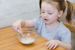 Little girl eats porridge stock photography