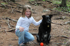 Little girl with dog. Little girl sits with her black dog and ball royalty free stock photography