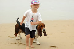 Little girl with dog. A beautiful little caucasian white blond girl child with cute expression in the face walking barefeet with her pet, a tricolor Basset Hound stock image