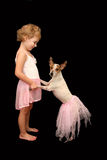 Little Girl and Dog Ballerinas. A little girl smiles at her dog while they dance in pink tutus Stock Images