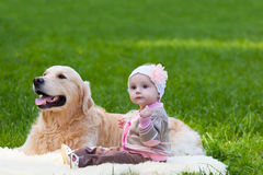Little girl and dog of breed a golden retriever. Sit on a green grass Royalty Free Stock Images