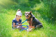 Little girl with dog. Happy little girl sitting with dog on the grass Royalty Free Stock Photo