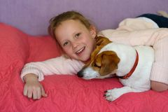 Little girl with dog at home in playroom. royalty free stock photography