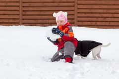 Little girl and dog playing with snow Royalty Free Stock Photo