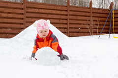 Little girl and dog playing with snow Stock Photos
