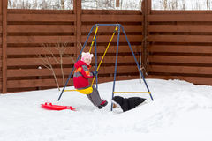 Little girl with a dog riding on a swing in snow Stock Images