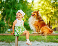 Little girl and dog sitting on a bench. Stock Photo