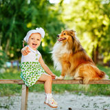 Little girl and dog sitting on a bench. Stock Photos