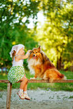 Little girl and dog sitting on a bench. Royalty Free Stock Images