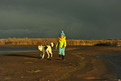 Little girl with dog on a sunset sandy autumn beach. Stock Photo