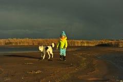 Little girl with dog on a sunset sandy autumn beach. Sunset on the coast of the Ladoga Lake Stock Photo