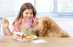 Little girl and dog at table having lunch smiling. Little girl having lunch at table, smiling dog sitting by her side stock image