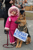 Little girl with dog with table translated from the Russian `Friends do not shoot!` in international action for the protection o. Volgograd, Russia - March 31 Stock Photo
