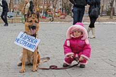 Little girl with dog with table translated from the Russian `Friends do not shoot!` in international action for the protection o. Volgograd, Russia - March 31 Royalty Free Stock Image