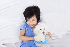 Little girl with doggy in the bedroom Stock Images