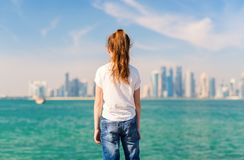 Little girl in Doha Qatar. Back view of little girl enjoying panoramic view of Doha Qatar skyline on sunny day Stock Images