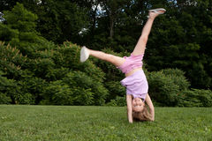Little girl doing a cartwheel Royalty Free Stock Images
