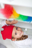 Little girl doing chores - dusting. And cleaning with feather duster Stock Image