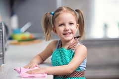 Little girl doing cleaning in the kitchen. At home royalty free stock photography