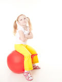 Little girl doing exercise with ball. Cute sly little girl doing gymnastic exercise with ball Stock Photo