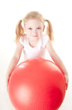 Little girl doing exercise with ball. Cute sly little girl doing gymnastic exercise with ball Royalty Free Stock Photos