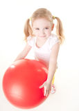 Little girl doing exercise with ball. Cute sly little girl doing gymnastic exercise with ball Royalty Free Stock Image