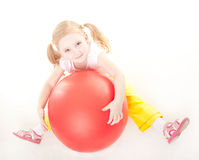 Little girl doing exercise with ball. Cute sly little girl doing gymnastic exercise with ball Royalty Free Stock Photo