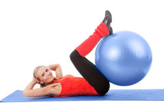 Little girl doing exercise with an instructor. Full body shot of a found beautiful woman doing exercise with a big medical ball . Red, blue and black colors Stock Photos