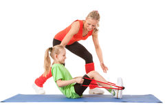Little girl doing exercise with an instructor. Full body shot of a little girl doing exercise with weights with an instructor on the mat. Orange, green and black Stock Photo