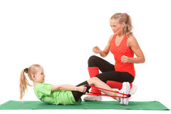Little girl doing exercise with an instructor. Full body shot of a little girl doing exercise with weights with an instructor on the mat . Orange, green and Royalty Free Stock Photography