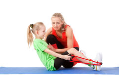 Little girl doing exercise with an instructor. Full body shot of a little girl doing exercise with weights with an instructor on the mat . Orange, green and Stock Photo