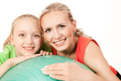 Little girl doing exercise with an instructor. Portrait of a little sport girl with an instructor . Orange, green and black colors Stock Image