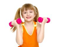 Little girl doing exercises with dumbbells. A cute little girl doing exercises with dumbbells. The concept of strength, health and sport. Isolated on white Royalty Free Stock Images
